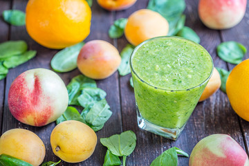 Blended Green Smoothies with Fruits and Spinach on Dark Wooden Background