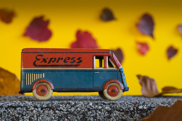 Van for express deliveries traveling in the fall. Antique toy car in autumn landscape.