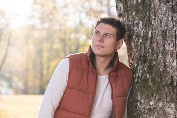Junger Mann lehnt an einem Baum im Herbst und denkt nach