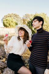 Una pareja joven en un evento social tomando vino muy atentos a algo que ocurre cerca