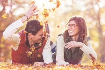 Junges Paar liegt im Herbstlaub und bewirft sich gegenseitig mit