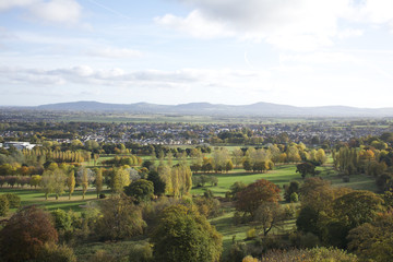 Abergele british village in wales, overlooking the town with mountains on the horizon, showing trees, fields and traffic from a high distant vantage point.