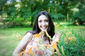 Nice girl standing near orange flowers and smiling