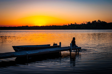 Tranquil silhouette of woman sitting on the dock on the shore of a calm lake in Minnesota