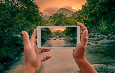 hands holding smart phone for photograph beautiful nature view of river mountain view in tropical forest.