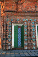 beautiful window with green shutters and ornate stone frame on o