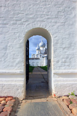 a small arched door in the large white stone wall and church beh