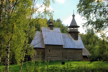beautiful old log wooden Russian Church on the green birches in