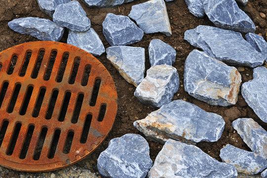 Kanalgitter mit Steinen