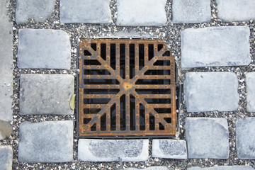Detail of a manhole grid in the street