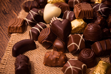 Assorted chocolates on wooden background