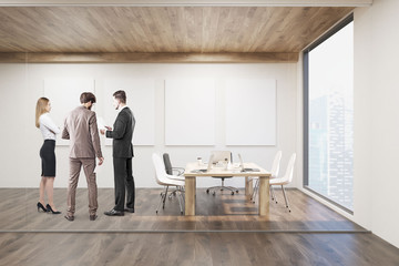 Businesspeople talking in conference room with four posters