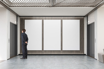 Man waiting for elevator in lobby with three large vertical post