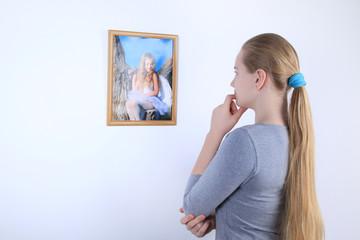 Teen girl standing near the wall looks photo