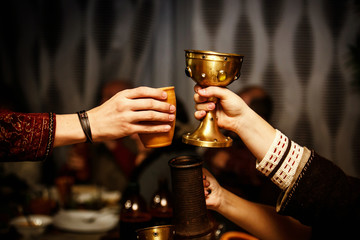 people clink cups on a medieval feast. Wall mural