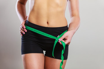 Fit woman measuring her hips with measure tape