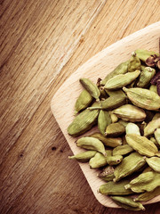 Green cardamom pods heap on wooden spoon