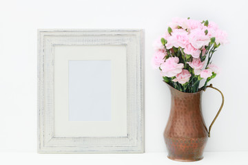 An empty white frame and a copper vase with miniature pink carnations on a white isolated background for adding text or a photo to use as a mock up for a business plan concept.