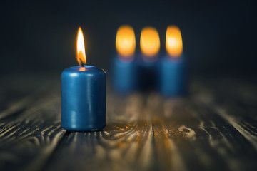 Lit four blue candles on wooden counter