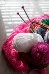 Ball of yarn and knitting needles in basket on a wooden grey table with window light. Close up. Top view. Handmade.