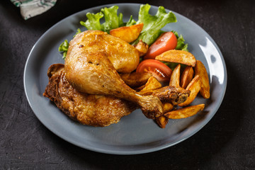 Roasted chicken legs with potato wedges and tomatoes