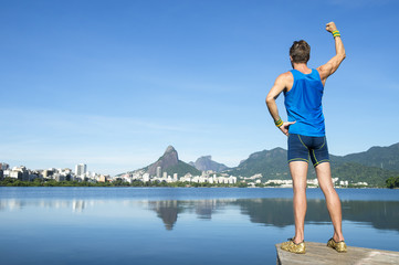Athlete in blue sport uniform standing with champion arm raised in a fist pump in front of the skyline at Lagoa Rodrigo de Freitas lagoon in Rio de Janeiro, Brazil