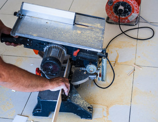 Closeup view of a man that is cutting wooden board electric circular saw. Focus is on the tools