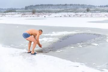 Fototapeta Winter swimming. Man in an ice-hole in outdoors