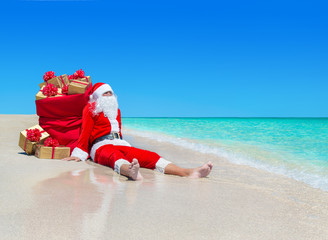Christmas Santa Claus with gift boxes sack at tropical beach