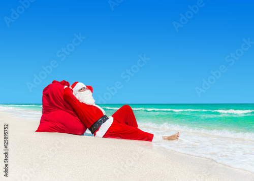 santa claus sunbathe on christmas gifts sack at ocean beach