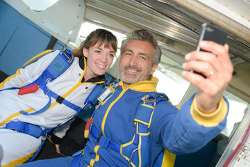 Male and female skydivers taking selfie