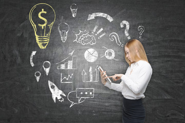 Woman with tablet computer and yellow dollar light bulb