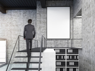 Man looking at wall in office with stairs and poster