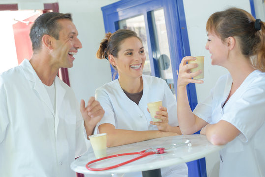 Medical staff laughing and drinking coffee