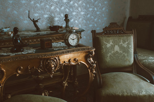 Details of vintage furniture with retro metal winding clock,  armchairs and wooden tables.