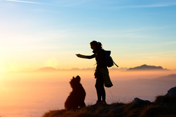 Girl plays with his dog in the mountain