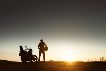 Biker's silhouette with motorcycle sunset