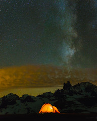 Red tent in the mountains under the clouds, stars and milky way.