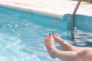 Woman legs on pool water