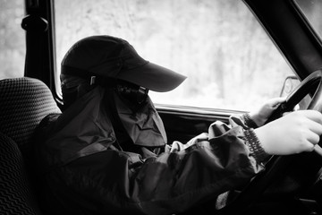 The boy in protective equipment sits behind the wheel of a car