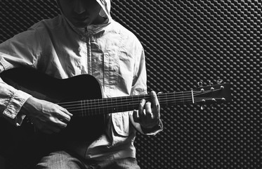BW asian guitarist playing acoustic guitar in recording studio