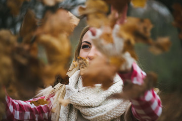 Portrait of a happy woman playing with autumn leaves outdoor