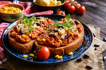 Fried toasts with chicken meat, tomato, chili, pepper, beans and
