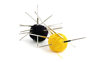 Two balls of yarn pierced with crochet hooks on white background