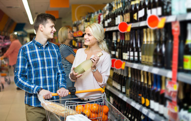сouple of customers purchasing at wine section in supermarket