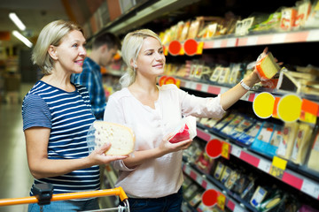 Adult girl with senior mother in cheese section of supermarket