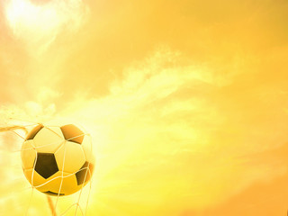 Football in goal net with warm yellow sky background