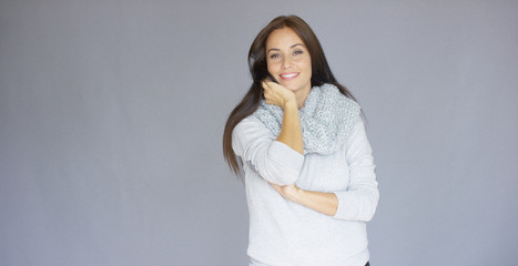 Gorgeous brunette woman posing isolated on gray background. She wearing sweatshir and woolen warm scarf. She is full of happiness. With a big smile on her face.