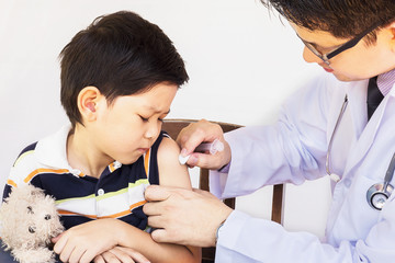 Sick Asian boy being treated by male doctor over white background