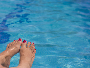 Woman feet on pool water